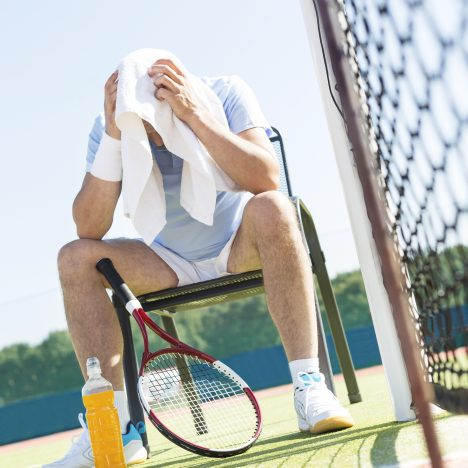 Full length of exhausted mature man with head in towel sitting on chair by net at tennis court on sunny day